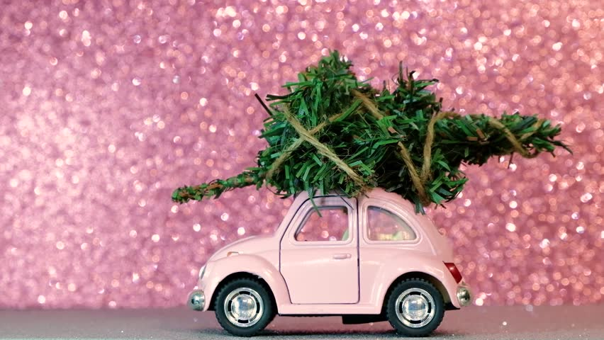 Omsk, Russia - Oktober 30, 2018: Toy model car with christmas tree on the roof rides on pink blurred glitter background. Delivery concept