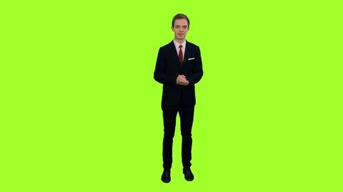 Young stylish presenter standing in studio and talking on green chroma key background, Front view, 4k pre-keyed footage