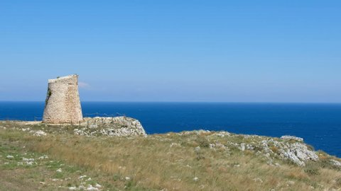 Salento countryside panoramic view panning watchtower coastal seascape grass Apulia Italy .