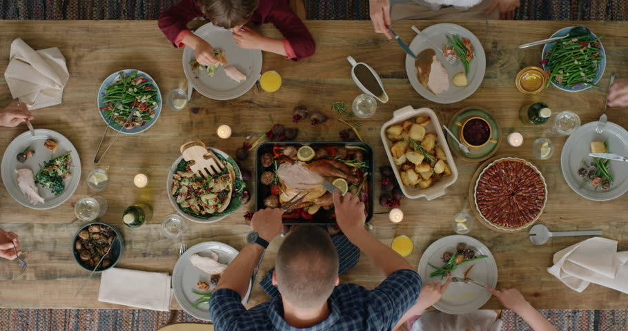 Happy family eating thanksgiving lunch together enjoying healthy homemade feast holiday celebration holiday meal overhead tracking