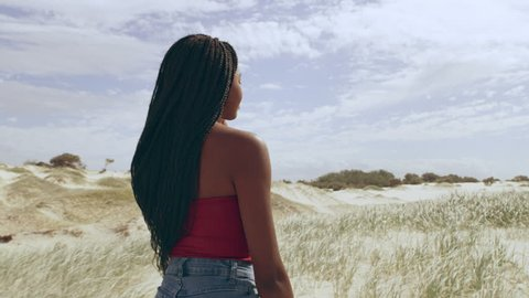 Young attractive girl walking among sand dunes smiling in Australia. Medium close on 4k RED camera.