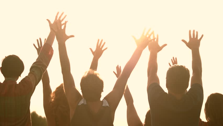 Silhouettes of people with raised hands at sunset. Group of friends enjoying of meeting sunset together. #1018960210