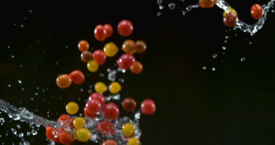 Crisp plump cherry tomatoes fall with water droplets on black background closeup in ultra slow motion with 4k Phantom Flex camera. | Shutterstock HD Video #1018965130