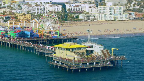 Aerial view of Santa Monica Pier shoreline on a sunny day in Los Angeles, California. Shot on 4K RED camera.