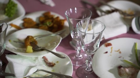 crumbs of dishes are on white plates on a pink background in the restaurant after the holiday. Leftovers