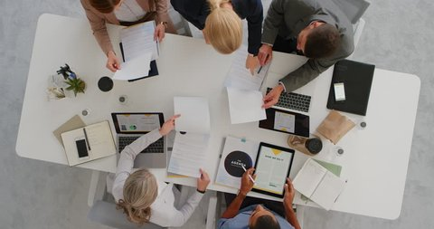 professional multi ethnic business team sharing ideas in boardroom meeting brainstorming corporate strategy using market statistics in documents top view