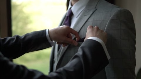 A young businessman straightens his colleague's handkerchief. An attractive man put a handkerchief in his jacket pocket. Man getting ready for a business meeting. Standing in front of the window