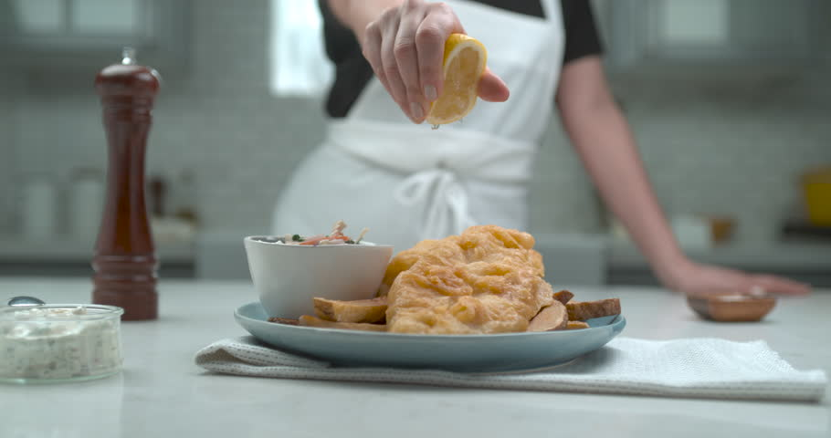 A chef squeezes a half cut lemon over plate of gourmet battered fish and chips in interior restaurant kitchen in soft light. Chef's Table and cooking show inspired footage Medium shot 4k Phantom Flex