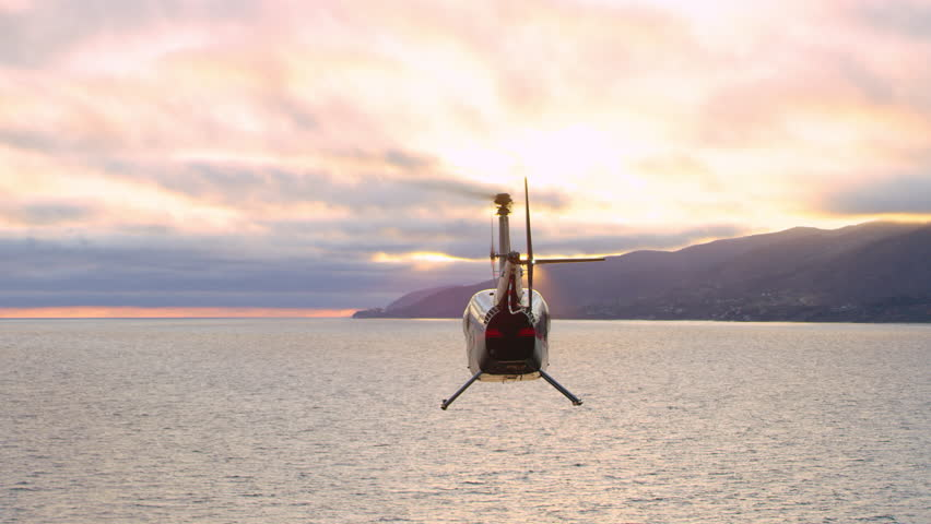 Aerial view of helicopter flying over ocean shoreline city with mountains in the distance during purple sunset in Los Angeles, California. Wide long shot on 4K RED camera. #1019021890