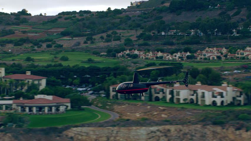 Aerial view of helicopter flying near ocean over cliff side mountain houses during a beautiful sunset in Los Angeles, California. Wide long shot on 4K RED camera.