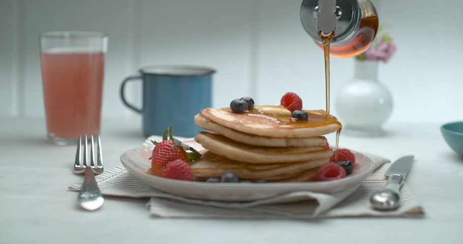 Maple syrup is poured over a stack of pancakes with fruit and butter on a table with a background in soft focus, in slow motion, in soft light. Closeup shot in 4K on a Phantom Flex | Shutterstock HD Video #1019032630
