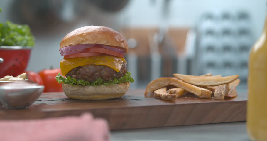 Crispy french fries dropping next to juicy cheeseburger on plate with sauce in ultra slow motion with 4k Phantom Flex camera | Shutterstock HD Video #1019032720
