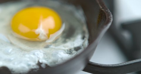 A chef fries an egg, sunny side up, in a small frying pan over an industrial gas burning stove with a shallow depth of field, in soft light, in slow motion. Closeup shot in 4K on a Phantom Flex camera