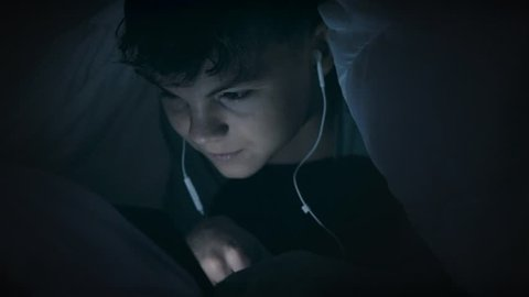Boy watching movie or playing games on tablet computer at night. Child with headphones lying down under blanket on bed using smartphone or tablet pc. Boy to make video call to talk to friends.