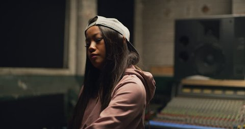 Funky dancer grooving to a track in a backwards baseball cap and pink hoodie dancing in front of professional mixing board in a music studio. Medium shot on 4K RED camera.