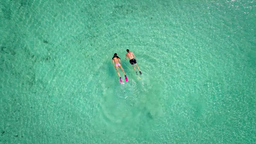 Aerial view of man and woman swimming and snorkeling with masks and flippers in clear sea.