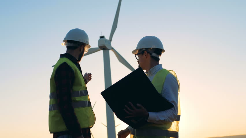 Two male experts are having a discussion in front of windmill. Clean, eco-friendly energy concept. | Shutterstock HD Video #1019164990