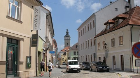 Ceske Budejovice, Czech Republic - MAY, 2018: car is moving on old narrow city street, tourists are walking