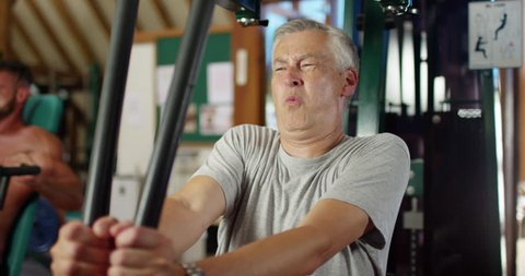 4K Funny gym concept - unfit mature man straining his muscles on weights machine. Slow motion.