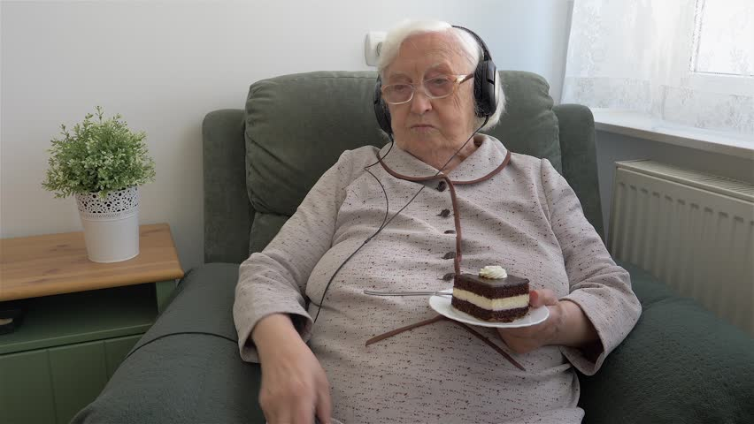 Old woman with a cake in hand is changing channels on TV