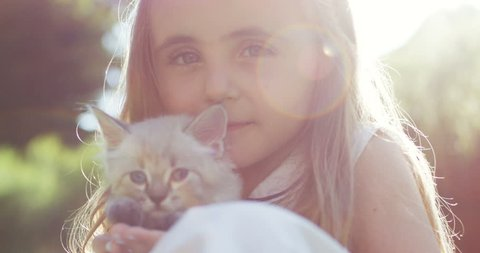 Portrait of the dreaming little sad blond teen girl hugging white fluffy kitty in the sunlight. Close up. Outdoors.