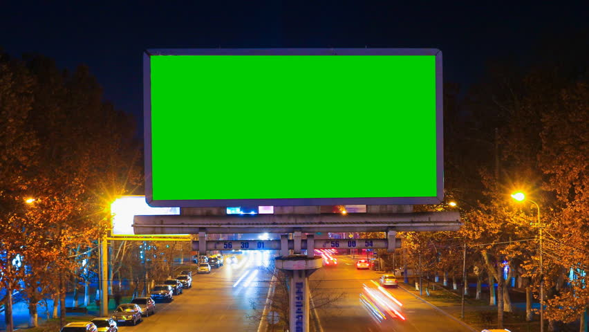 A billboard with green chroma key on a background of a city night landscape of fast moving cars with long exposure. Time Lapse video. | Shutterstock HD Video #1019243590