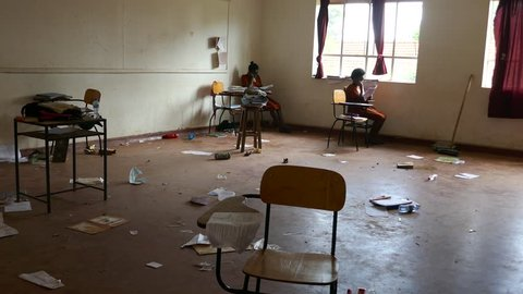 Kampala/Uganda - November 2018: Girl students are sitting in a chaotic empty classroom, reading and study for the national exam.
