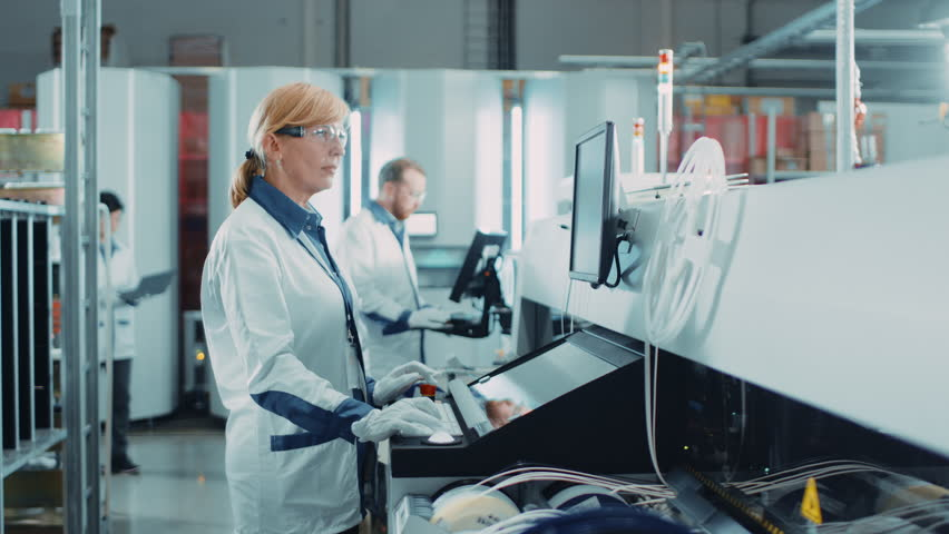 On High Tech Factory Female Engineer Uses Computer for Programing Pick and Place Electronic Machinery for Printed Circuit Board Surface Mount Assembly Line. Production of PCB with SMT Machinery. | Shutterstock HD Video #1019311900