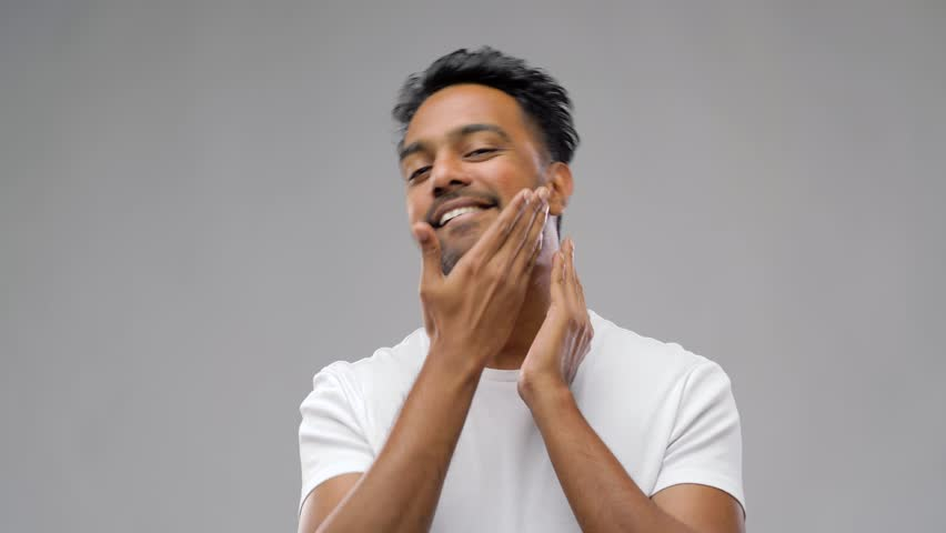 Grooming and people concept - smiling indian man touching his beard or applying aftershave over gray background | Shutterstock HD Video #1019318830