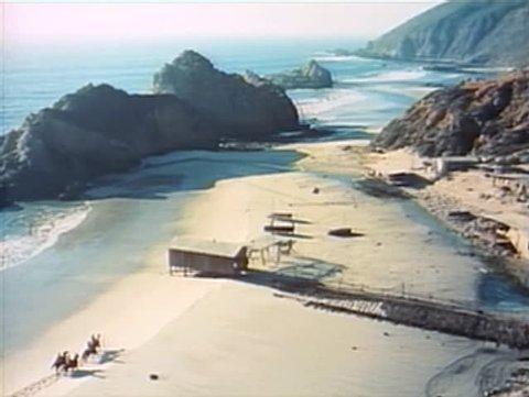 High angle view men riding horses along California beach, 1960s