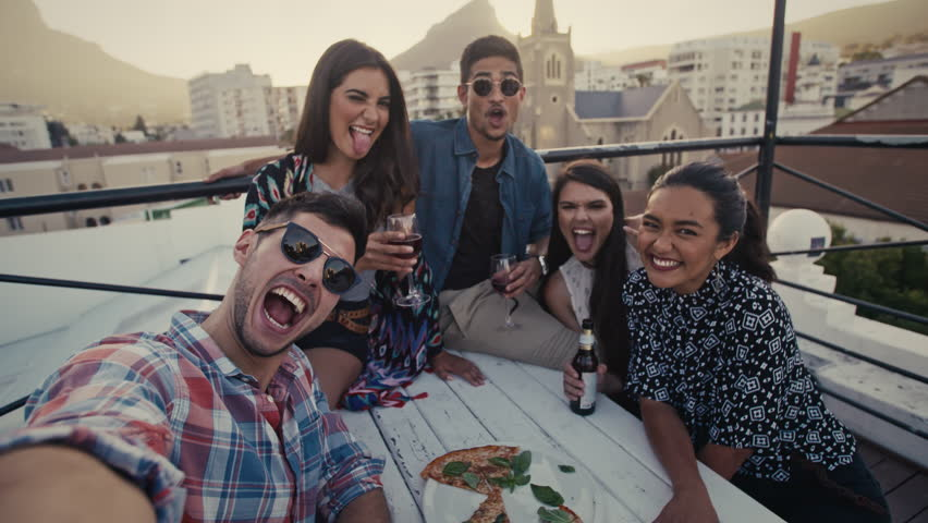 Multi-ethnic young people making a selfie at terrace party. Friends taking self portrait during party on rooftop.  | Shutterstock HD Video #1019329870