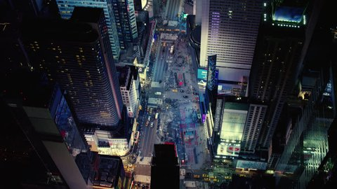 Top down aerial view of busy streets and lights in downtown Manhattan in Times Square, New York City, with bright night lighting. Wide shot on 4k RED camera with green screens.
