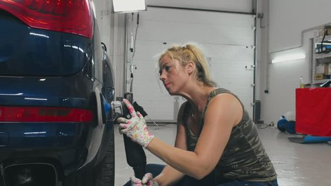 Woman worker making car body polishing with polisher in service. Woman service worker making waxing car after car wash. Car body work