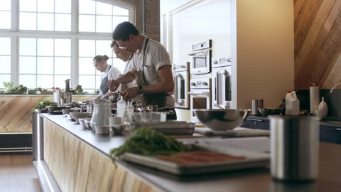 Three professional chefs cooking and preparing food on a large countertop, in interior kitchen with soft day lighting. Medium shot on 4k RED camera.