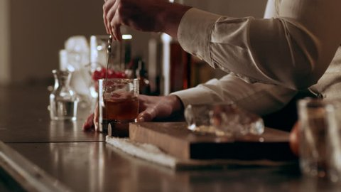 Old school mixologist stirring the liquid in a glass with a long spoon in interior classy bar with soft interior lighting. Close up shot on 4k RED camera.
