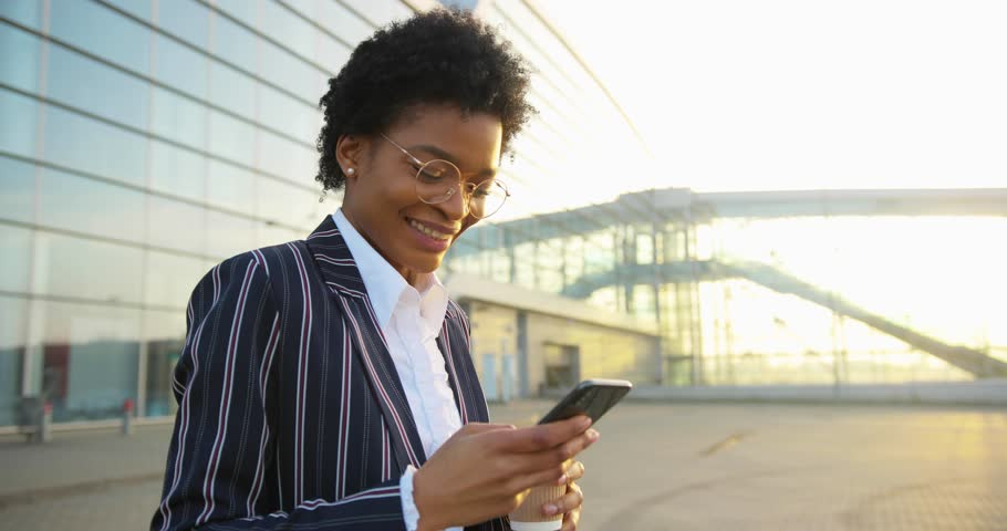 4k. Slow motion. Charming African American woman smiles while she reads something in her phone and drinks her coffee-to-go walking before modern building in the rays of evening sun #1019443000