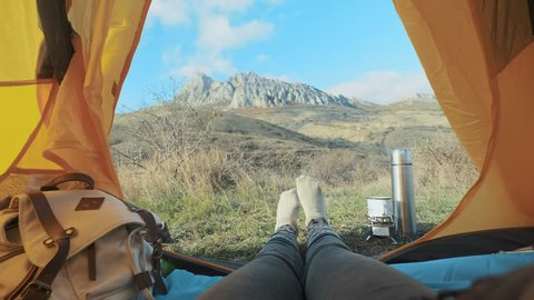 Camping woman lying in tent Close up of Girl feet wearing hiking boots relaxing on vacation. From the tent view of the big mountains. Hiking lifestyle during summer. Traveling alone in the mountains