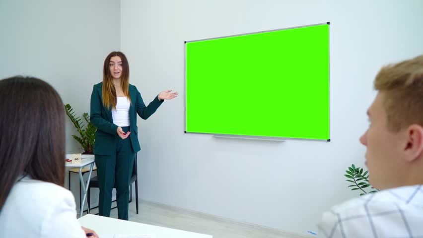 young happy teacher near with a green screen board teaching students in classroom. interactive education, practice, learning, education, knowledge concept