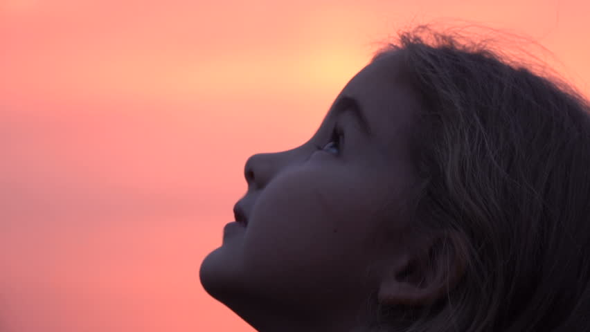 Kid looking up at the sky in nature. Little girl praying looking up at purple sky with hope, close-up.  #1019722660