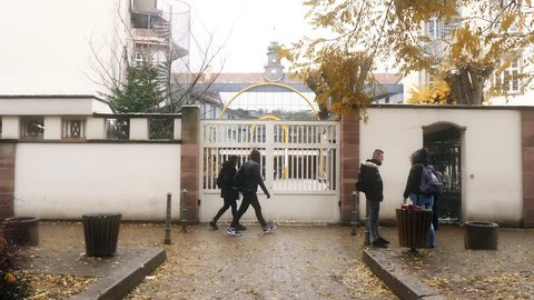 STRASBOURG, FRANCE - CIRCA 2018: Entrance door to the Lycee prive Sainte-Clotilde lyceum in Strasbourg with young boys and girls outdoor cold winter day - French education institution building