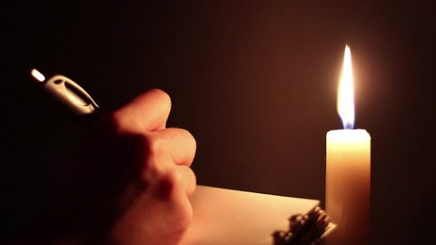 women's hands write in a notebook recording in the dark near the candle