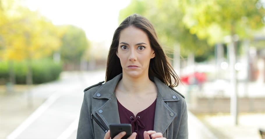 Front view of a perplexed woman walking checking smart phone content and then stops looking at camera in a park | Shutterstock HD Video #1019750350