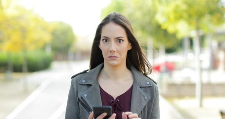 Front view of a perplexed woman walking checking smart phone content and then stops looking at camera in a park