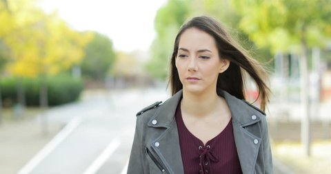 Front view of a serious pensive woman walking towards camera looking at side in a park