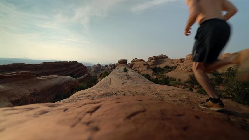 Man jogging on rocks in Utah desert at sunset for health and wellness | Shutterstock HD Video #1019780740