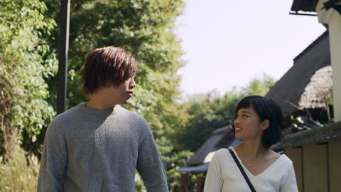 Young happy couple walking, flirting, and discussing down a sidewalk in Kyoto, Japan with soft natural lighting.  Shot on a RED 4K camera on a gimbal.