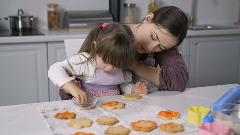 Concentrated little girl with down syndrome decorating gingerbread with icing in the kitchen. Caring mother teaching child with special needs baking and decorating homemade cookies with royal icing.