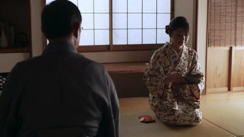 Floral pattern kimono wearing female drinking a bowl of hot tea in a traditional Japanese room with soft day lighting. Medium shot on 4k RED camera.