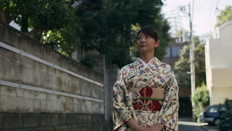 Peaceful woman in kimono walking and looking up and around a quiet residential street  in Japan, with soft day lighting. Medium shot on 4k RED camera.
