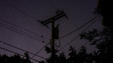 A time-lapse of the stars rotating in the sky behind a silhouetted suburban telephone pole and power lines and trees in the night sky.